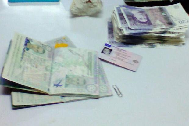 An image shows the passports of the arrested men and forged 20-pound notes. (Photo by Bangkok Post Suphapong Chaolan)
